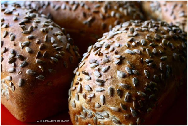 bunch of breads with sunflower seeds on top