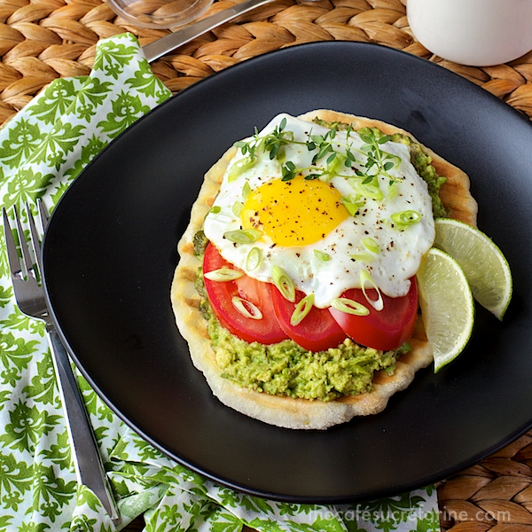 Photo of a black plate with Avocado Breakfast Flatbreads on it on a wicker table and a green and white patterned napkin underneath the plate.