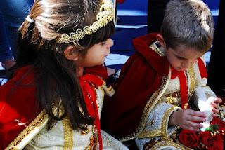 Fotografia colorida feita por Hisao Shirabiyoshi. Nela aparecem duas crianças, uma menina e um menino, caracterizados de rei e rainha, com manto vermelho com detalhes e ela com tiara dourada. Ele segura a pomba branca - símbolo do Divino Espírito Santo enquanto conversam sentados e descansam do desfile da festa popular.