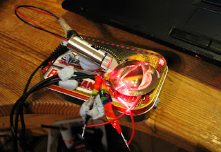 [Image: A mess of wires and components attached to a mint tin using blu-tack. A laser module is pointing at a piezzo buzzer at an acute angle. A piece of mirror is glued onto the piezo buzzer. The laser and piezzo buzzer are connected to wires that lead out of the picture.]