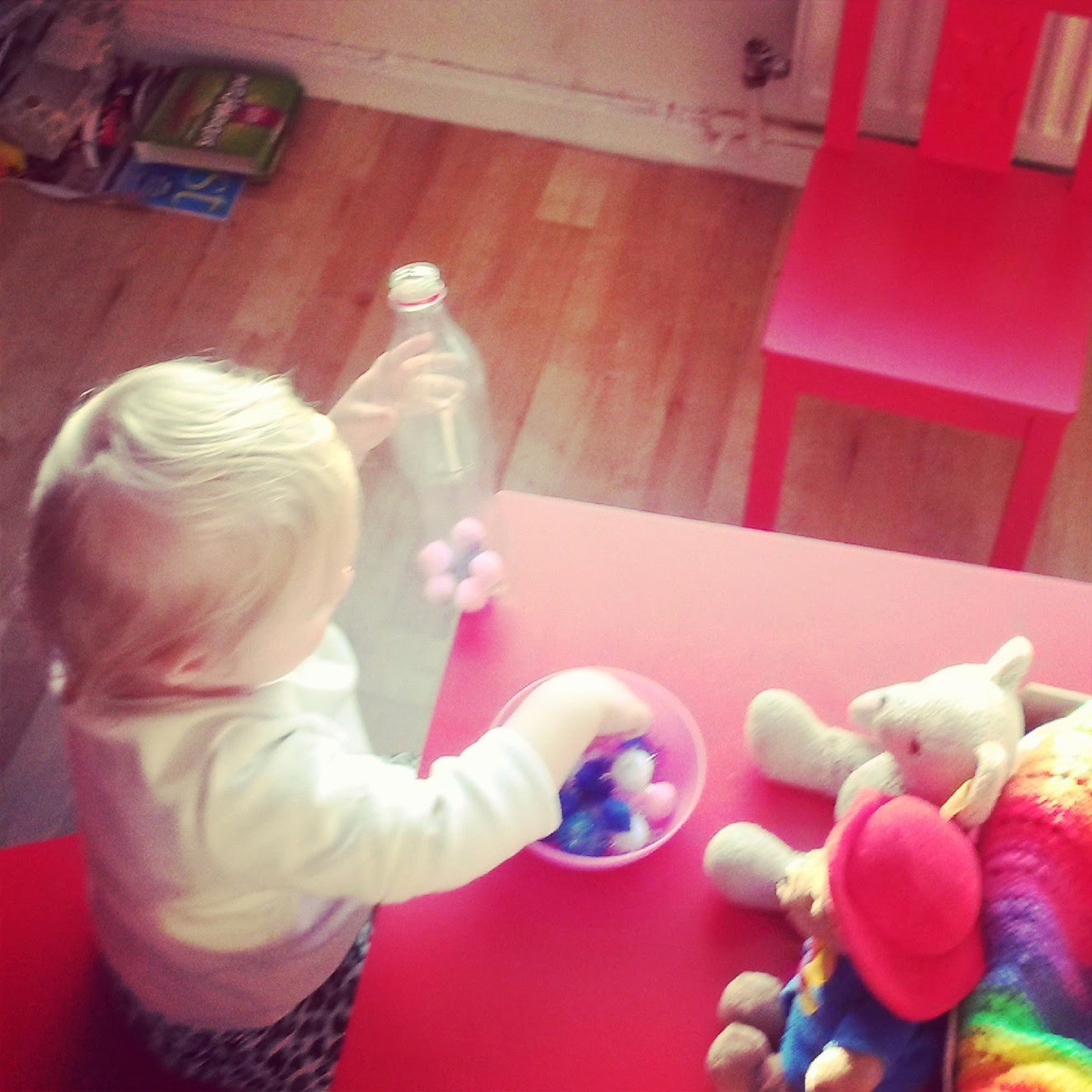 toddler putting pom poms in a bottle