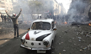 An Egyptian protester flashes the V-sign for victory as he stands near a car with the hood painted in the colours of the national flag