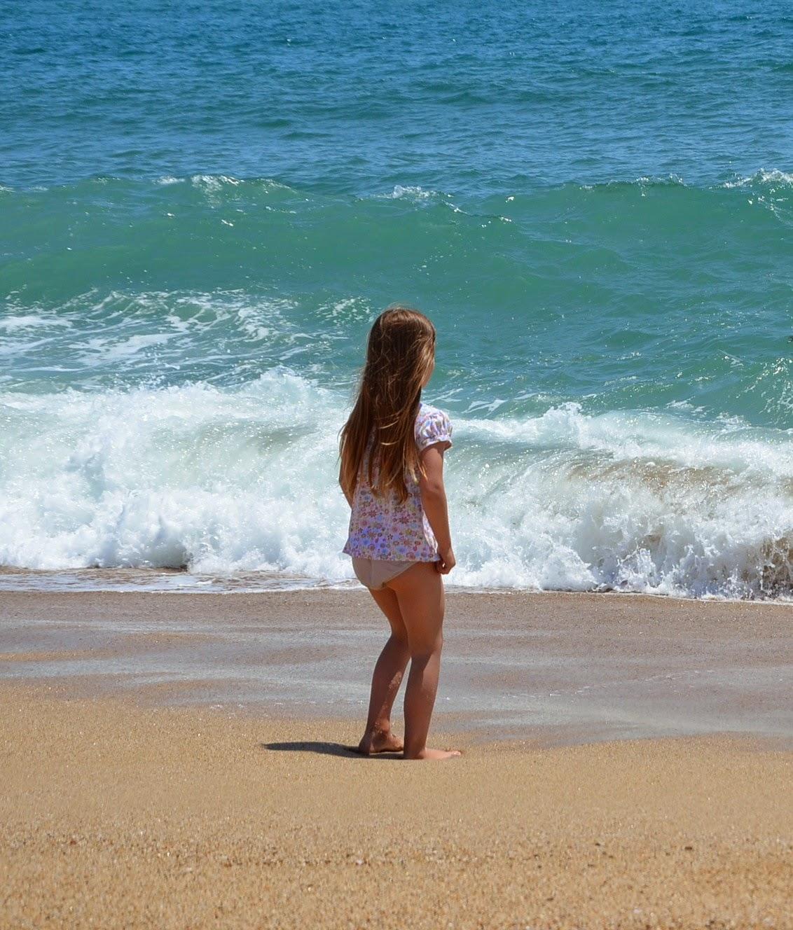 Kind steht am Strand