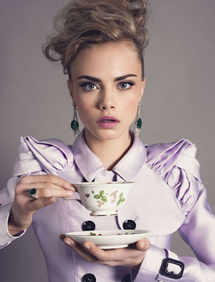 model Cara Delevingne posing in a lilac pastel coat, preparing to sip tea.