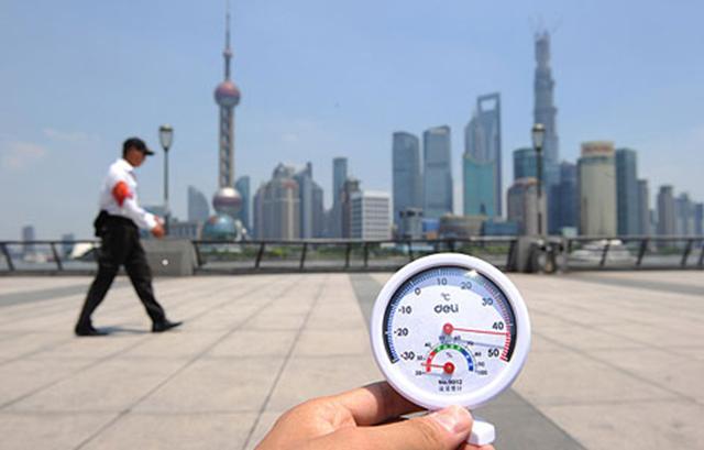 Một anh nhân viên an ninh đang làm nhiệm vụ trong ánh nắng Mặt Trời như thiêu đốt dọc theo Bến Thượng Hải và một nhiệt kế với số chỉ là 42°C. Ảnh : AP Images.