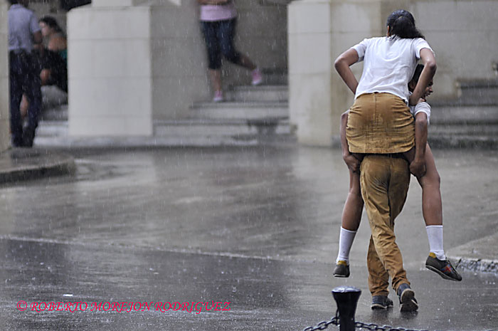 Muchachos de enseñanza secundaria juegan bajo la lluvia de la tarde del 15 de febrero de 2013 cuando un frente frío amenaza con llegar a La Habana  Roberto MOREJON RODRIGUEZ