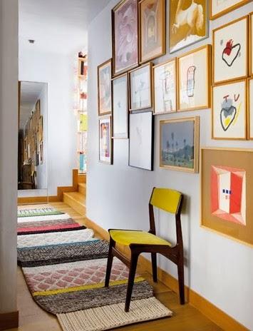 Biały przedpokój i kolorowy chodnik, żółte krzesło, kolorowe grafiki na białej ścianie, grafiki Mercedes Perez de Castro