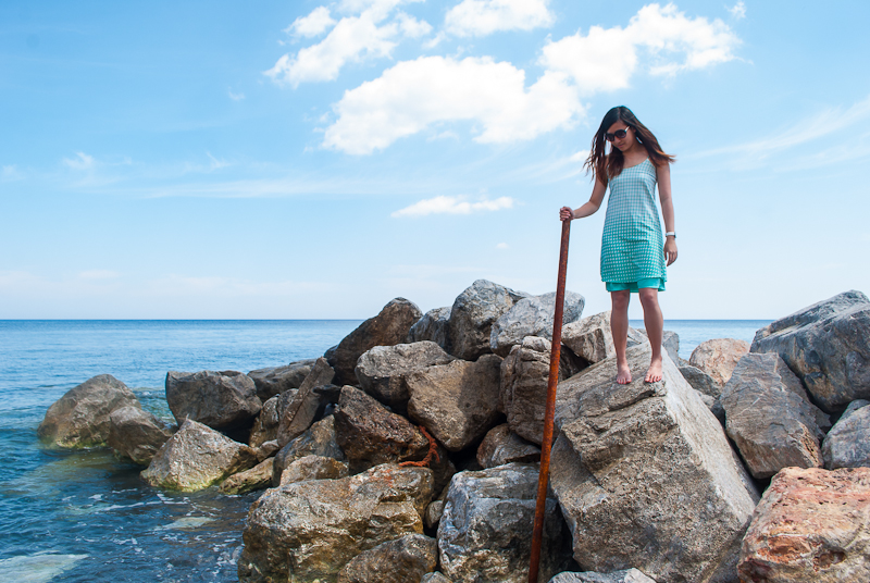 rocks and waves or perissa beach with outfit of the day in santorini, greece