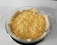 shredded cheese on flattened bread in pie plate