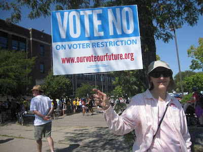 Woman holding official Vote No on Election Restrictions sign