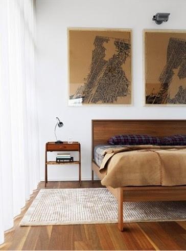 framed antique maps hung as art in bedroom