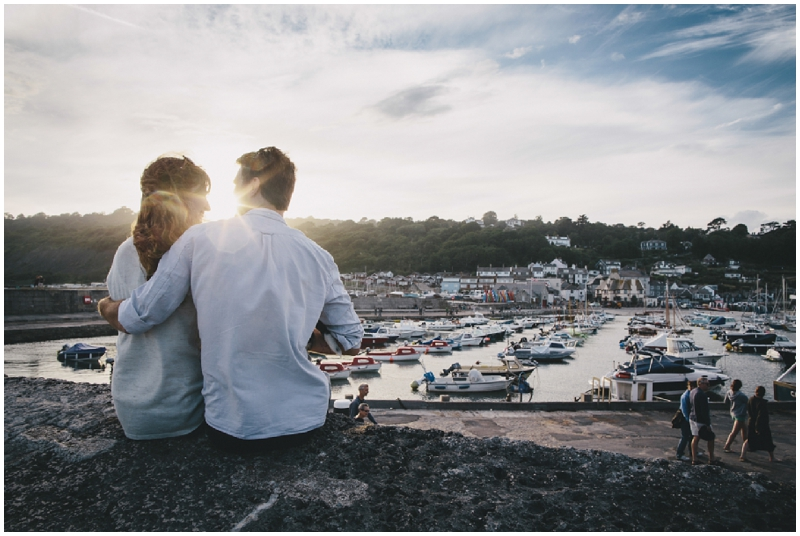 Couple at sunset sitting by Lyme Regis harbour