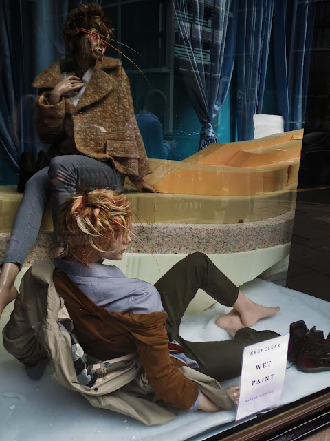 Male and female mannequin lie on foam in the window of Harvey Nichols