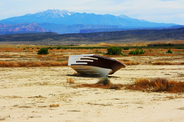 An old ski boat sitting in the Utah desert near Arches National Park.
