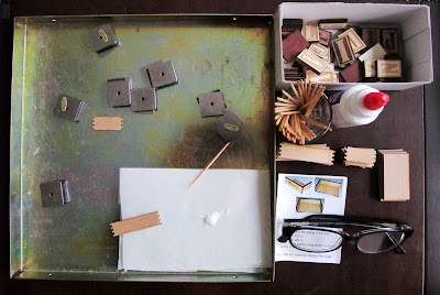A magnetic gluing jig, box of wooden alphabet  tiles, glue, toothpicks, kit pieces, instructions and reading glases laid out on a dining table.