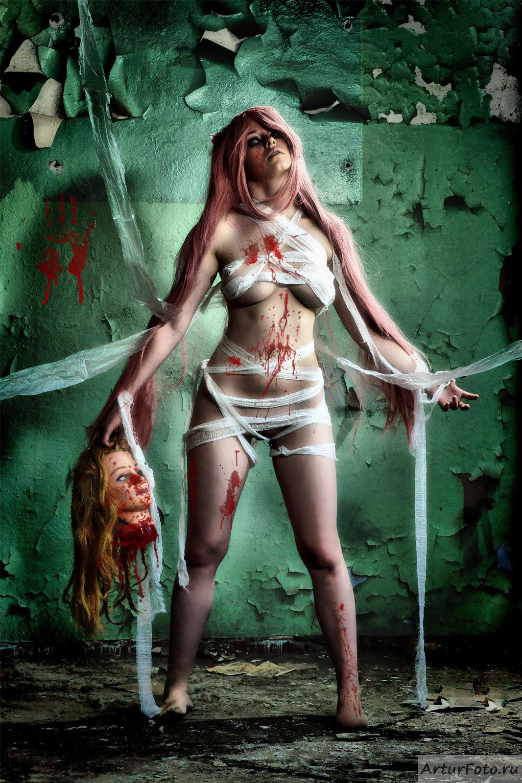 cosplay trash d'une jeune  couverte que de bandes tenant une fausse tête décapité