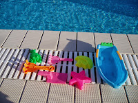 pool toys in the sunshine by the edge of the pool