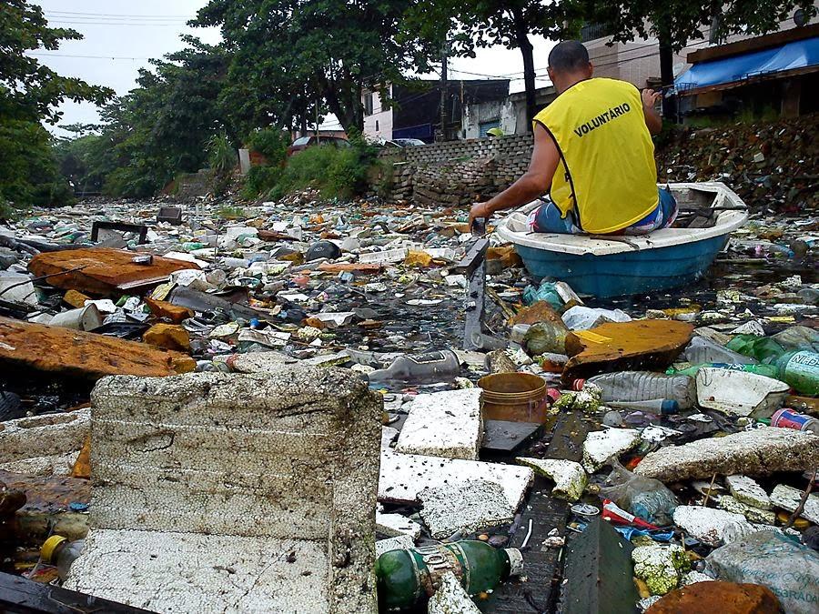 Voluntário retira resíduos do canal em São Vicente. Crédito: Instituto EcoFaxina