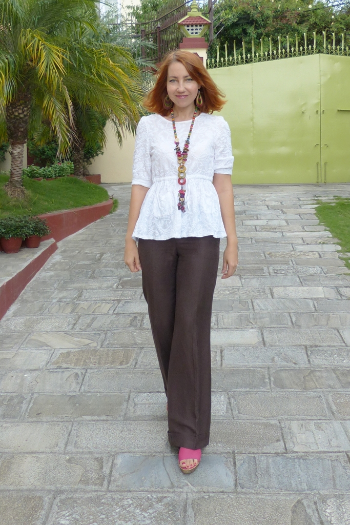 White cotton top, brown linen trousers and wooden necklace