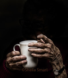 Aged hands holding a mug
