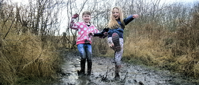 two girls splashing in muddy puddle wellies