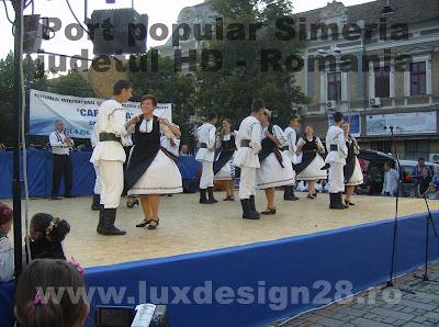 Perechi de dansatori imbracati in costume populare din zona Simeria, Romania