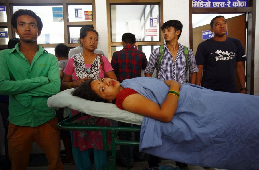 A landslide victim waits for treatment at a hospital in Katmandu, Nepal, Saturday, Aug. 2, 2014. A massive landslide killed at least eight people and blocked a mountain river in northern Nepal on Saturday, causing the water to form a lake that was threatening to burst and sweep several villages, officials said.