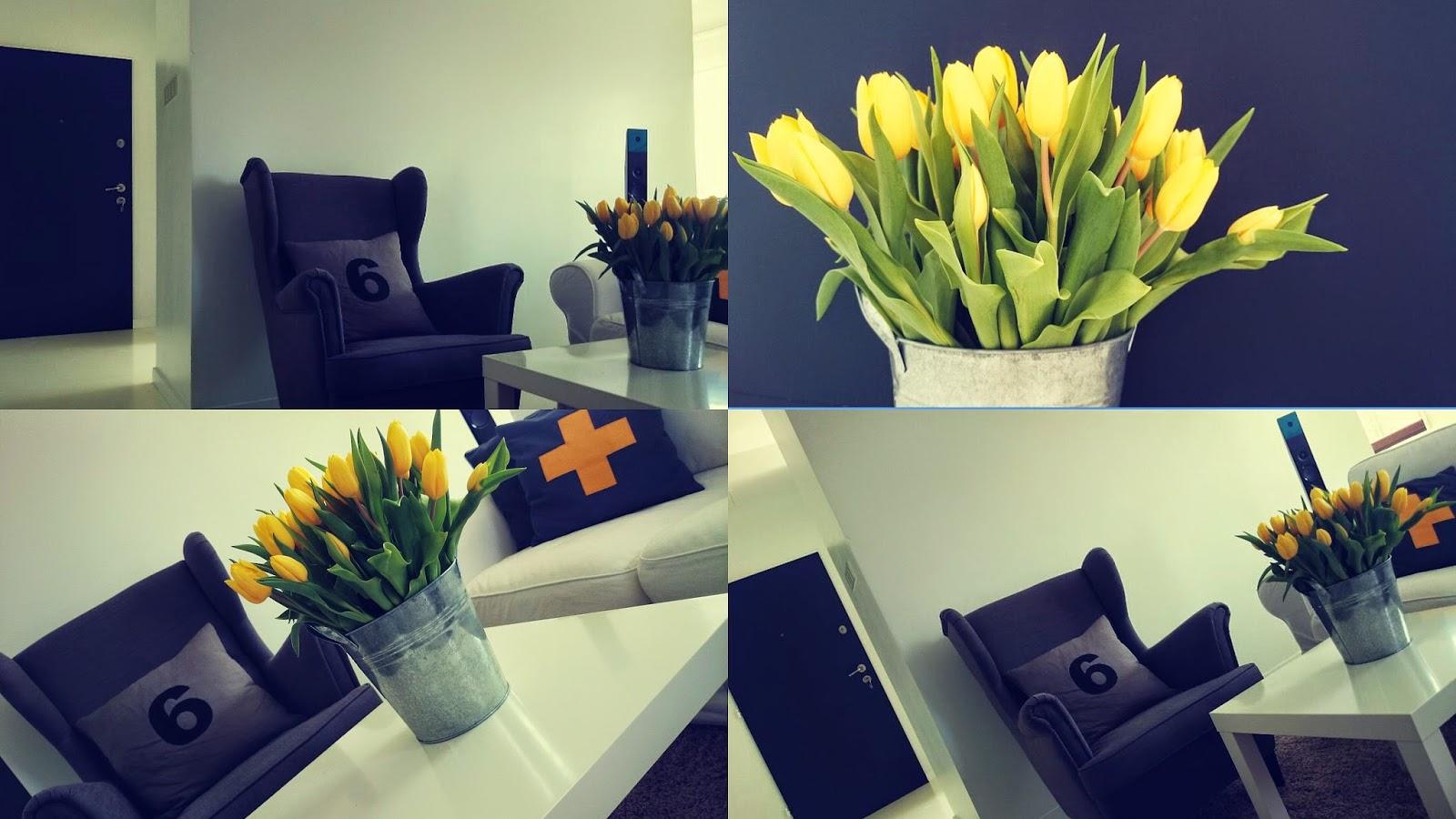 Drzwi pomalowane farbą tablicową, szary fotel uszatek, biała podłoga z wylewki, żółte tulipany w ocynkownaym wiadrze