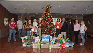 Faculty and staff from the College of Criminal Justice pose with presents under the Colleges Christmas Tree