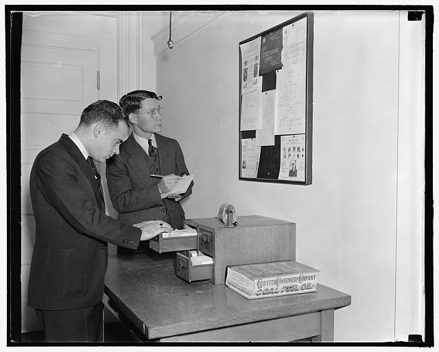 Employees of the Secret Service checking over bulletin board getting latest criminal news, 10/38