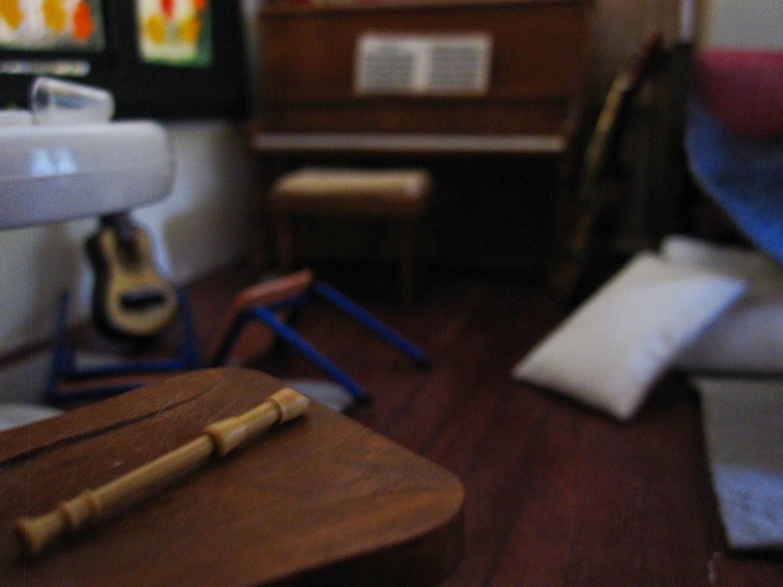 Modern dolls' house miniature post-party scene showing a piano, guitar and recorder, plus a broken chair.