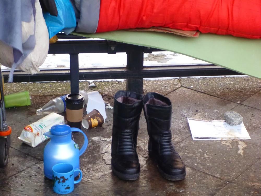 Winterstiefel, Thermoskanne, Teetasse, Getränkeflaschen, Kaffeepappbecher und ein mit einem Stein beschwerter Zettel