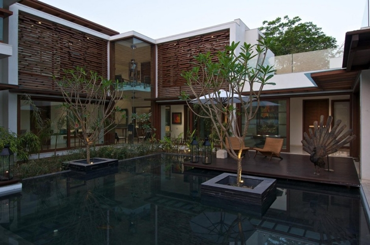 Pond and trees in front of Courtyard Home by Hiren Patel Architects