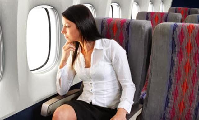 wanita duduk di pesawat menikmati penerbangan