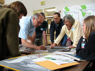 Photo of six individuals holding a discussion around a map