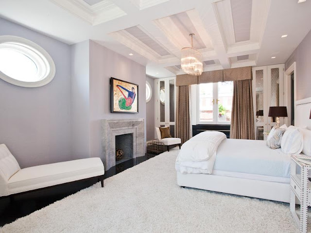 Master bedroom with coffered ceiling, black floor, large white shag rug, white chaise longue, lavender walls, a fireplace, chandelier, built in white cabinets with glass fronts, light brown curtains and oval windows