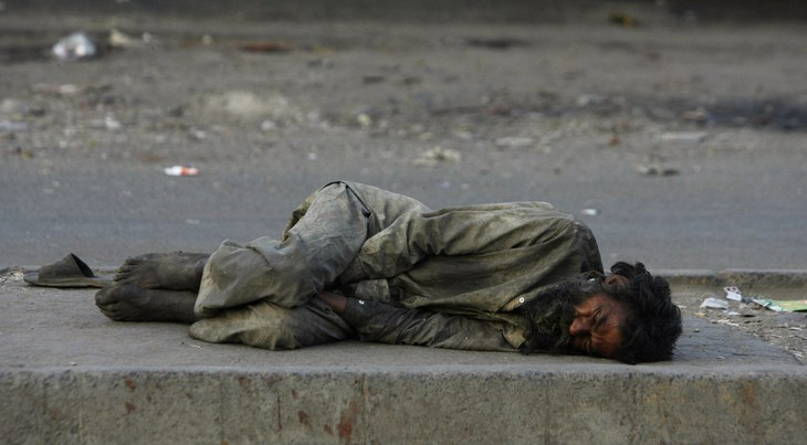 a homeless man lying on the side of the road