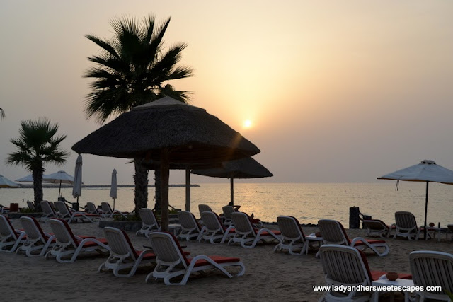 Sun loungers and the beach at The Cove Rotana
