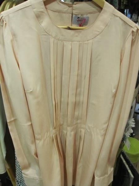 Blusa beige con plisado y manga larga.
