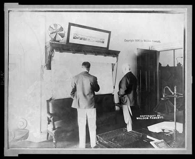 1906: U.S. Secret Service Chief John E. Wilkie examining map in his office