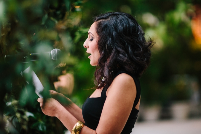 groom's sister doing a reading at the outdoor wedding ceremony