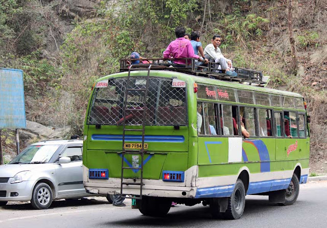 people sitting on the roof of a bus