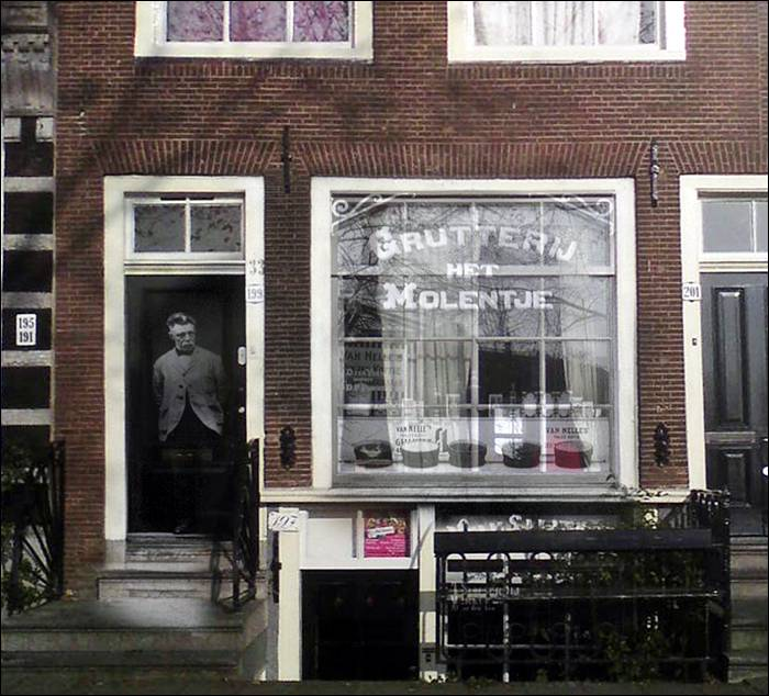 """Shopkeeper standing in front of his shop."""