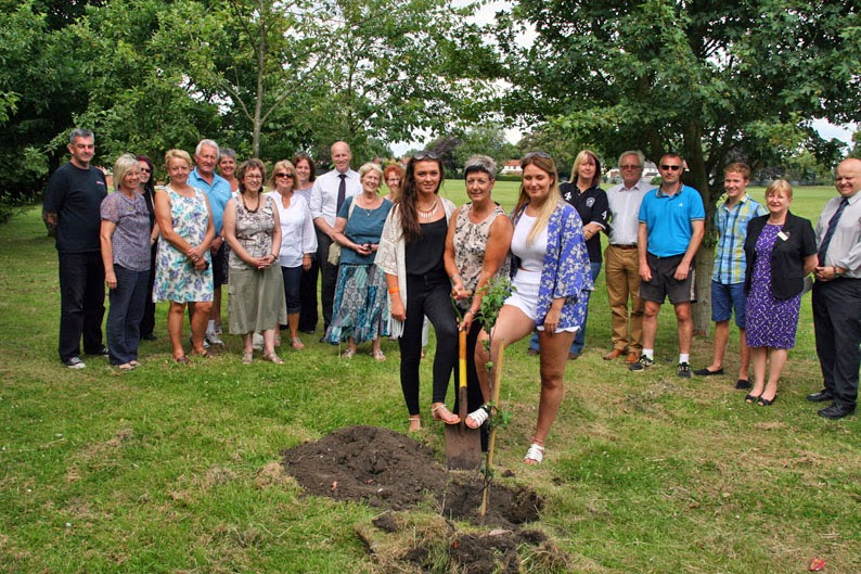 Jane Gibbons, centre, plants a tree in memory of Adrian Gibbons, long-serving teacher at Sir John Nelthorpe School, Brigg, flanked by daughters Kelly (left) and Lucy.