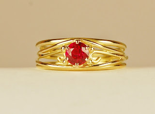 18k wirey yellow gold ring with round ruby.