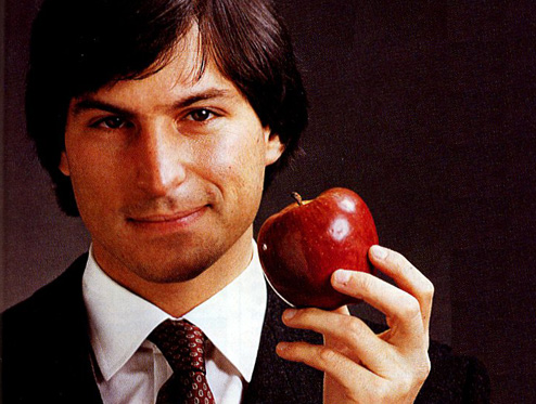 steve jobs smiling and holding an apple