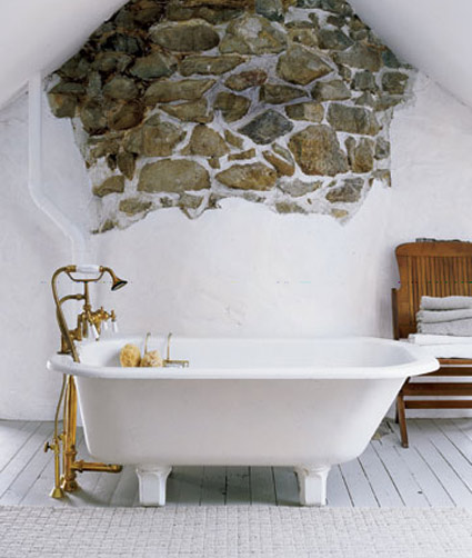 clawfoot bathtub with exposed rock wall