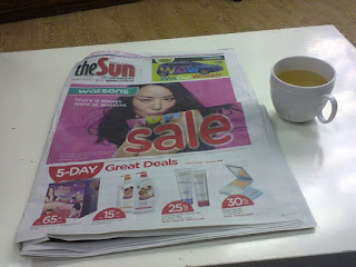 cup of honey green tea and newspaper