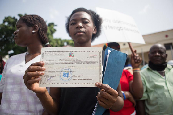 Elena Lorac, a spokesperson form the Reconoci.do movement, shows a birth certificate issued by the Central Electoral Board, during a rally in front of the Presidential Palace in Santo Domingo, July 13, 2013. (Fran Afonso)