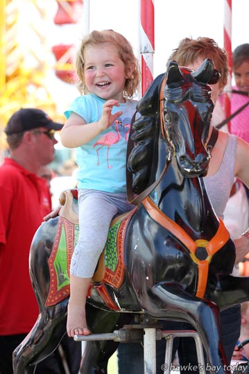 Lara Thompson, 2, Cambridge, on the merry-go-round, one of the sideshows run by Mahon Amusements. photograph